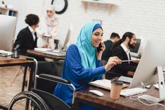 Disabled arab woman in wheelchair working in office. Woman is working on desktop computer and talking on phone. Disabled arab women in hijab in wheelchair Royalty Free Stock Image