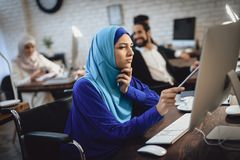 Disabled arab woman in wheelchair working in office. Woman is working on desktop computer. Disabled arab women in hijab in wheelchair working in office. Woman royalty free stock photography