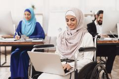 Disabled arab woman in wheelchair working in office. Woman is working on laptop. Stock Image