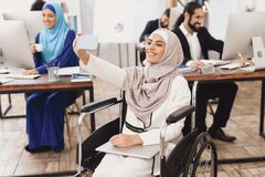 Disabled arab woman in wheelchair working in office. Woman is taking selfie. royalty free stock photos