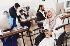 Disabled arab woman in wheelchair working in office. Woman is talking on phone and drinking coffee. Disabled arab women in hijab in wheelchair working in office Stock Images