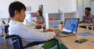 Disabled Asian male executive using laptop at desk in modern office 4k. Side view of disabled Asian male executive using laptop at desk in modern office. Multi stock video footage