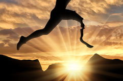 Disabled athlete with prosthetic leg jumping across rock on sunset royalty free stock photography