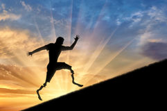 Disabled athlete with prosthetic legs to climb up sunset. Disabled runner with prosthetic legs to rise up on background sunset . Concept disability and sport Stock Photos