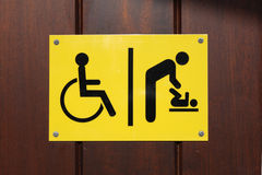 Disabled and baby changing sign. Yellow and black disabled and baby changing sign stock image