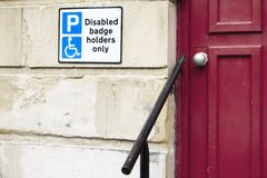Disabled badge holders only sign and rail for accessible assistance to help old senior people and wheelchair users. Uk stock photos