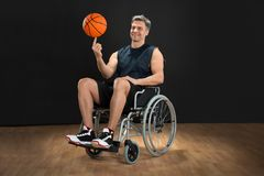 Disabled basketball player spinning ball. Disabled Basketball Player On Wheelchair Spinning Ball On His Finger Royalty Free Stock Photography