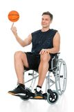 Disabled basketball player spinning ball. Disabled Basketball Player On Wheelchair Spinning Ball On His Finger Over White Background Royalty Free Stock Images