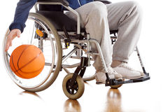 Disabled basketball player. A disabled basketball player in a tracksuit with a ball Stock Image