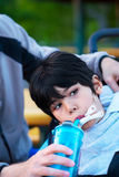 Disabled biracial little boy in wheelchair drinking water from s Stock Photos