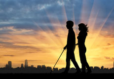 Disabled blind goes with cane and nurse near city sunset Stock Images