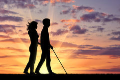 Disabled blind goes with cane and nurse sunset Royalty Free Stock Images