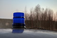 Disabled blue flasher on the roof of the car. From the flasher stretches the wire. Against the sky and blurred trees. Evening.  Selective focus royalty free stock photography