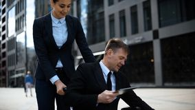 Disabled boss on wheelchair and his woman employee working with digital pad. stock footage