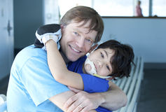Disabled boy giving father a big hug. Disabled five year old boy giving father a big hug Stock Image