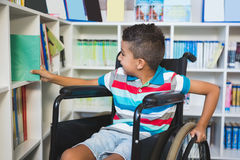 Disabled boy selecting a book from bookshelf in library Stock Photos