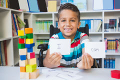 Disabled boy showing placard that reads I Can in library Royalty Free Stock Photo