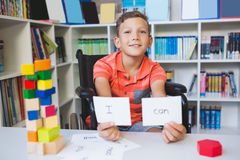 Disabled boy showing placard that reads I Can in library Stock Photography
