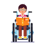 Disabled boy sitting in a wheelchair and reading Stock Photo