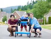 Disabled boy in walker, with father and brother Stock Images