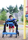 Disabled boy in walker at inaccessible pla. Disabled boy in walker walking up to a handicap inaccessible playground Stock Photo