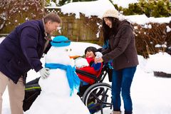 Disabled boy in wheelchair building snowman with family during winter stock image