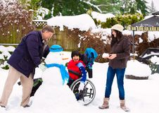 Disabled boy in wheelchair building snowman with family during winter royalty free stock photos