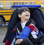 Disabled boy in wheelchair, by bus. Disabled five year old boy in wheelchair, by schoolbus Stock Image
