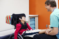 Disabled boy in wheelchair with doctor. Disabled boy in wheelchair sharing laugh with his doctor or therapist Stock Photo