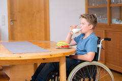 Disabled boy in wheelchair is drinking milk and eating Royalty Free Stock Images