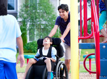 Disabled boy in wheelchair enjoying watching friends play at par Royalty Free Stock Image