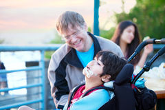 Disabled boy in wheelchair enjoying watching friends play at par Royalty Free Stock Images