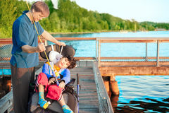 Disabled boy in wheelchair fishing with father Stock Photos