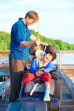 Disabled boy in wheelchair fishing with father Stock Image