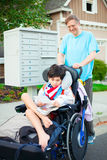 Disabled boy in wheelchair getting mail from mailbox with father Stock Photography