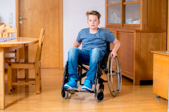 Disabled boy in wheelchair at home. In the living room Royalty Free Stock Images