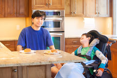 Disabled boy in wheelchair eating with brother Royalty Free Stock Photo