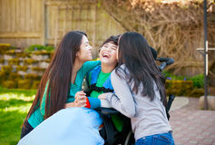 Disabled boy in wheelchair laughing with teen sister on patio Royalty Free Stock Photo