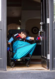Disabled boy in wheelchair opening front door Stock Images