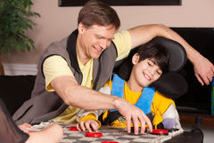 Disabled boy in wheelchair playing checkers with father at home Royalty Free Stock Images