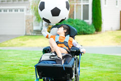 Disabled boy in wheelchair playing with soccer ball at park Stock Images