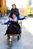 Disabled boy in wheelchair running  with caregiver outdoors Royalty Free Stock Images