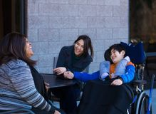 Disabled boy in wheelchair at table outdoors talking with caregi. Eleven year old disabled biracial Asian Caucasian boy in wheelchair outdoors, sitting and Stock Photography