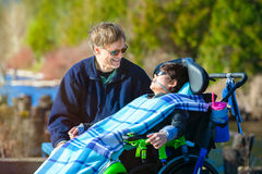 Disabled boy in wheelchair talking with father at lakeside park Stock Image