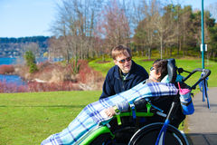Disabled boy in wheelchair talking with father at lakeside park Stock Images