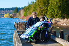 Disabled boy in wheelchair talking with father at lakeside park Stock Photo