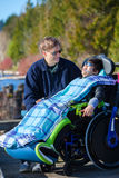 Disabled boy in wheelchair talking with father at lakeside park Stock Photos