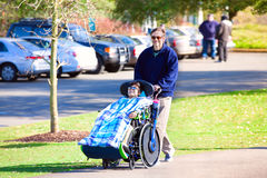 Disabled boy in wheelchair walking at park with father Royalty Free Stock Photos