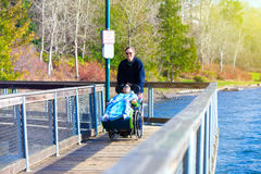 Disabled boy in wheelchair walking at park with father Royalty Free Stock Photo