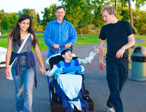 Disabled boy in wheelchair walking at park together with family Stock Photos